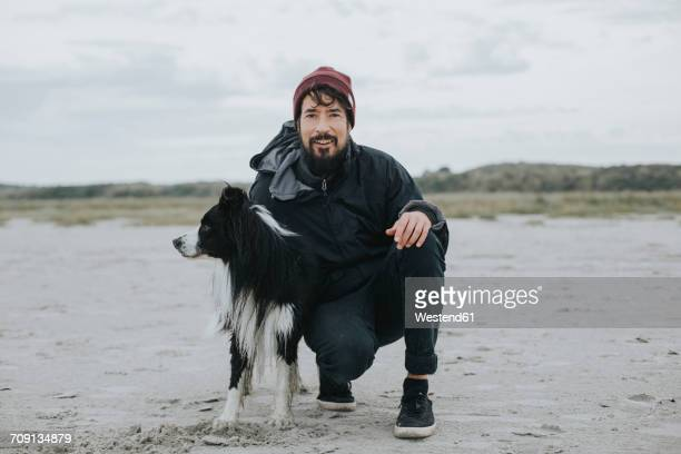Netherlands, Schiermonnikoog, man with Border Collie on the beach