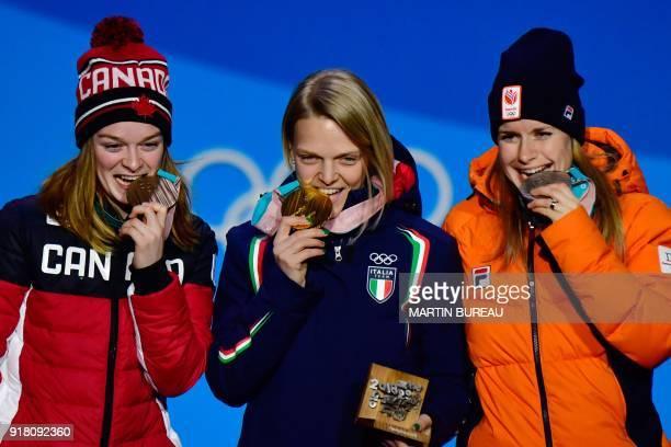 Netherlands' silver medallist Yara Van Kerkhof Italy's gold medallist Arianna Fontana and Canada's bronze medallist Kim Boutin bite their medals on...