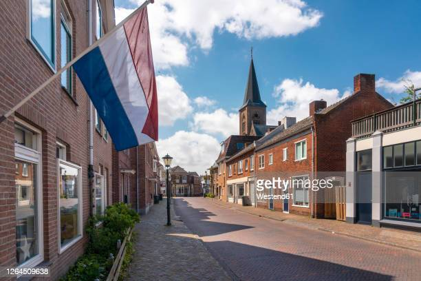 netherlands, south holland, noordwijk, dutch flag fluttering over empty town street - netherlands stock pictures, royalty-free photos & images
