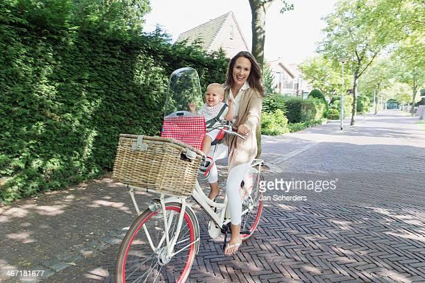 netherlands, south holland, oud-beijerland, mother with her baby daughter (12-17 months) on bicycle - holländische kultur stock-fotos und bilder
