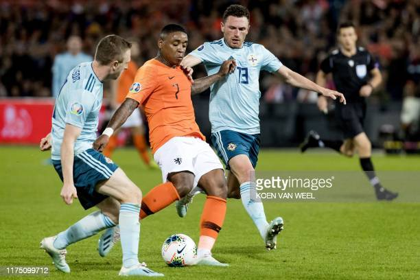 Netherlands' Steven Bergwijn vies for the ball with Northern Ireland's Corry Evans and Shane Ferguson during the UEFA Euro 2020 group C qualifying...