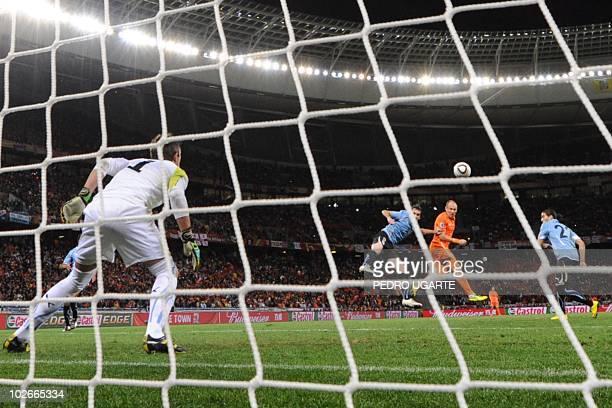 Netherlands' striker Arjen Robben heads the ball to score his team's third goal on Uruguay's goalkeeper Fernando Muslera during the 2010 World Cup...