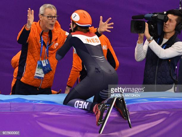 TOPSHOT Netherlands' Suzanne Schulting celebrates winning with coach Arie Koops the women's 1000m short track speed skating A final event during the...