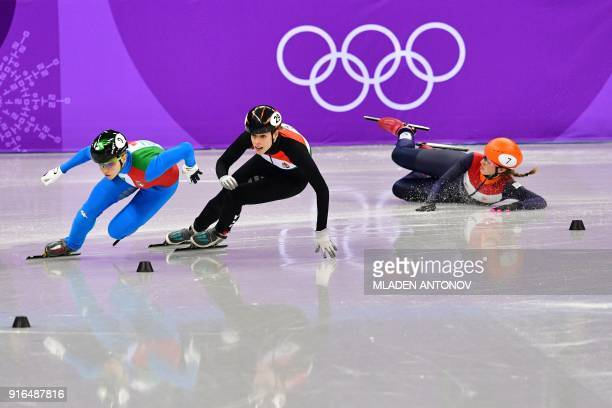 Netherlands' Suzanne Schulting falls beside Italy's Arianna Fontana and Hungary's Andrea Keszler in the women's 500m short track speed skating heat...