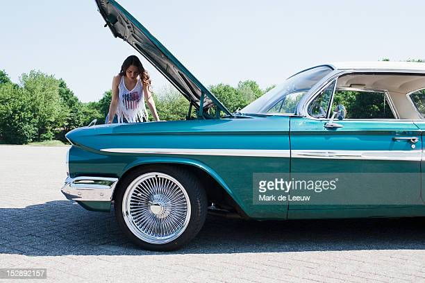 Netherlands, Tilburg, Woman standing near broken vintage car