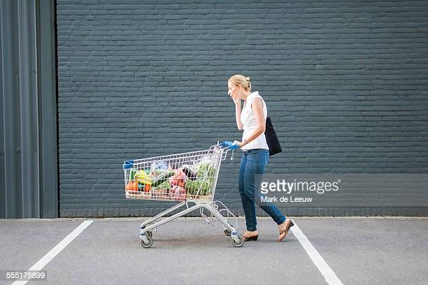 netherlands, tilburg, woman walking with shopping cart - shopping cart stock pictures, royalty-free photos & images
