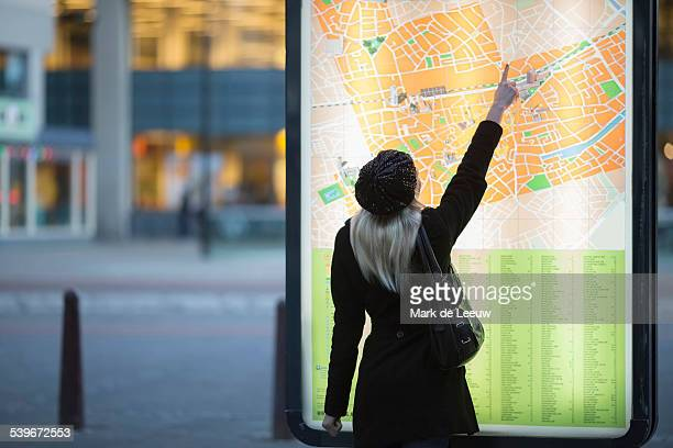 Netherlands, Tilburg, Young woman pointing at city map