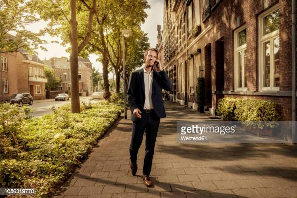 netherlands, venlo, businessman on cell phone walking on pavement - adulto de idade mediana - fotografias e filmes do acervo