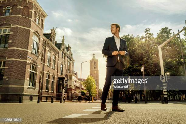 netherlands, venlo, businessman standing on a street - low angle view stock pictures, royalty-free photos & images