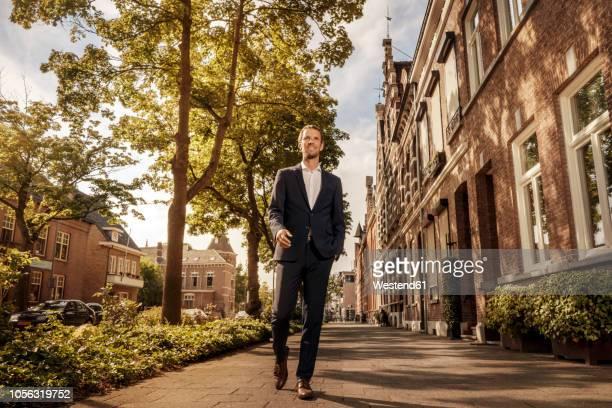 netherlands, venlo, confident businessman walking on pavement - laag camerastandpunt stockfoto's en -beelden
