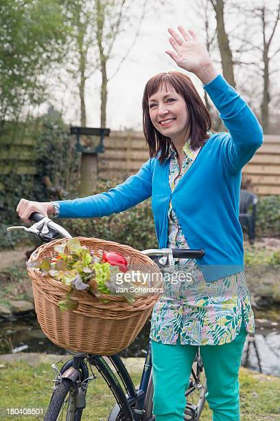 Netherlands, Venlo, Mature woman with fresh vegetables in bike basket
