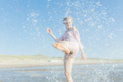 Netherlands, young woman splashing water at the beach in summer - gettyimageskorea