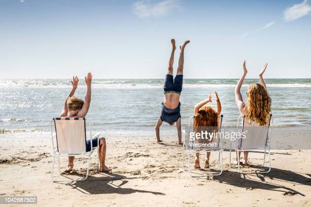 netherlands, zandvoort, family clapping hands for father doing a handstand on the beach - beach fun stock pictures, royalty-free photos & images