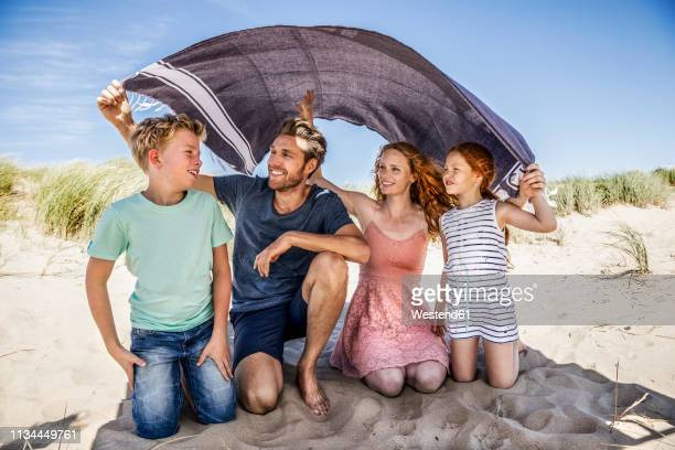 netherlands, zandvoort, happy family under a blanket on the beach - beschützer stock-fotos und bilder