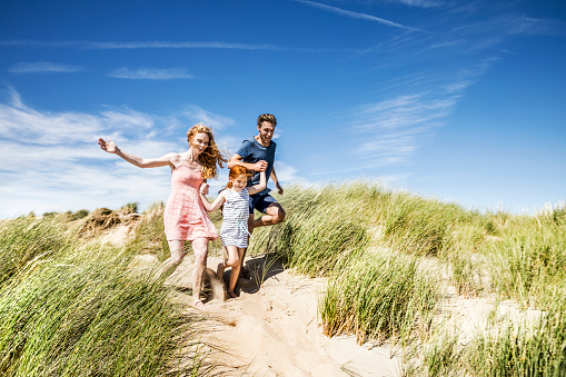 Netherlands, Zandvoort, happy family with daughter running in beach dunes - gettyimageskorea