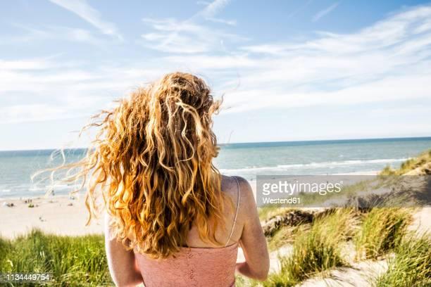 netherlands, zandvoort, woman standing in dunes - noordzee stockfoto's en -beelden