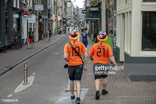 Netherlands's football team supporters walk in the streets of Amsterdam, on June 17, 2021 prior to the UEFA EURO 2020 football match between...