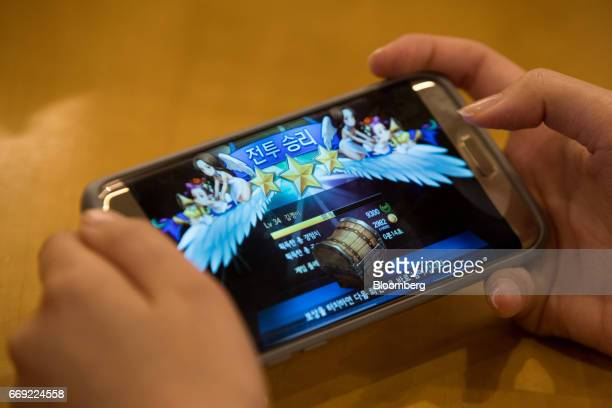 Netmarble Games Corp. Employee plays the Seven Knights mobile role-playing game on a smartphone in the cafeteria at the company's headquarters in...