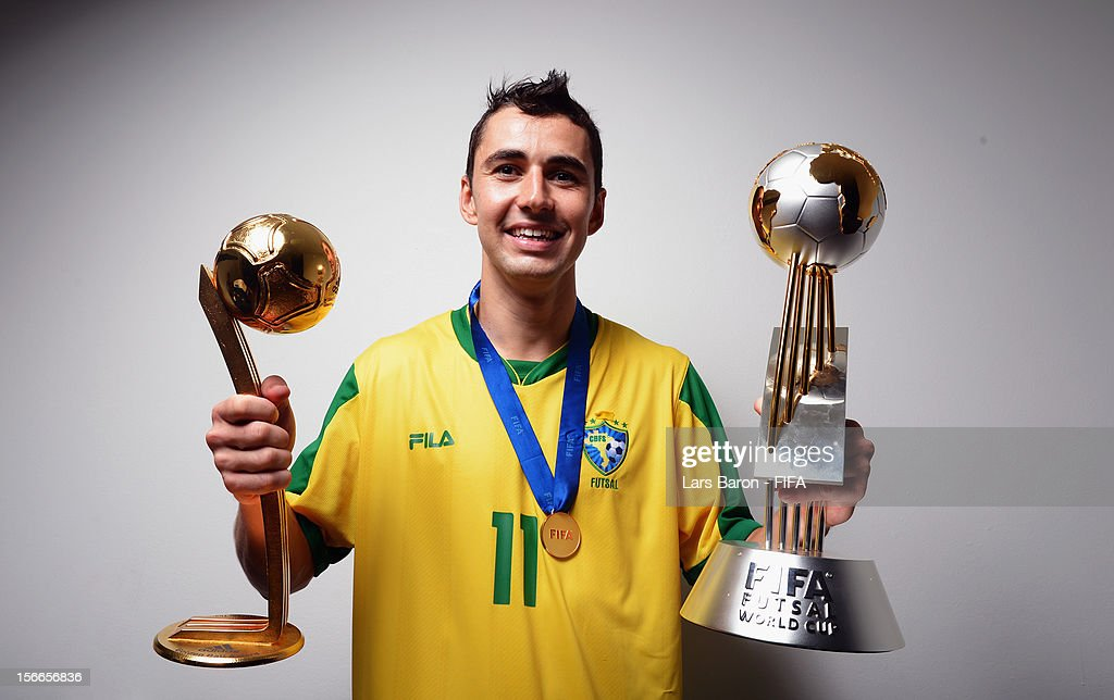 Neto of Brazil poses with the trophies in the locker room after winning the FIFA Futsal World Cup Final at Indoor Stadium Huamark on November 18, 2012 in Bangkok, Thailand.