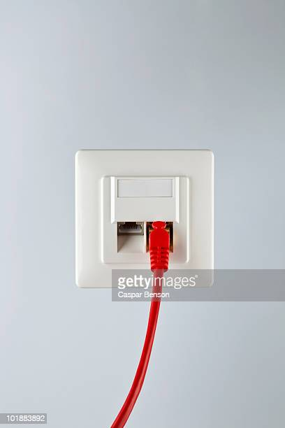 A network cable plugged into a wall socket