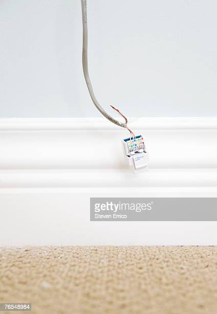 Network Connection Plug and cable hanging from wall