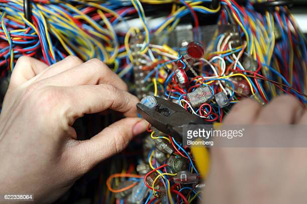 A network engineer from Openreach a unit of BT Group Plc connects wires inside a primary connection point box in this arranged photograph in...
