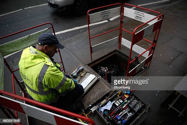 A network engineer from Openreach a unit of BT Group Plc inspects cables inside an access cover beneath a sidewalk in London UK on Wednesday Dec 17...