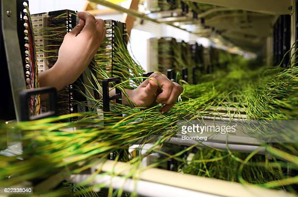 A network engineer from Openreach a unit of BT Group Plc secures a wire into a communications rack inside an exchange building in this arranged...