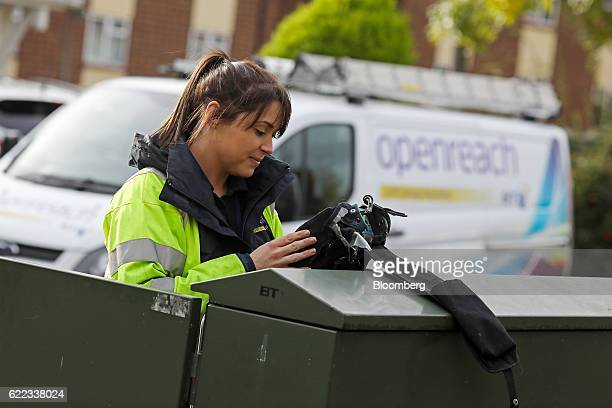 A network engineer from Openreach a unit of BT Group Plc tests a residential telephone line from a primary connection point box in this arranged...