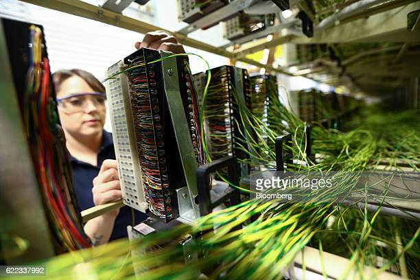 A network engineer from Openreach a unit of BT Group Plc works on copper jumper wires inside an exchange building in this arranged photograph in...