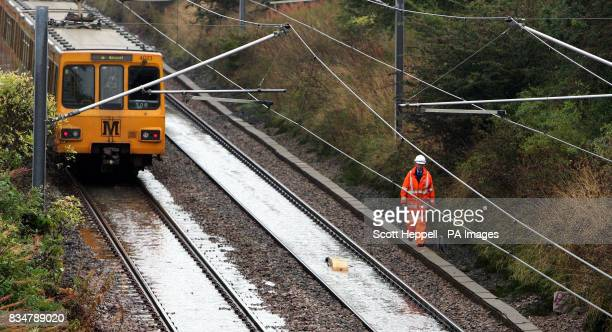 Network Rail Inspector, checking flooded track' as a metro train slowly travels past at Wardley in Gateshead, where heavy rain has put a speed...