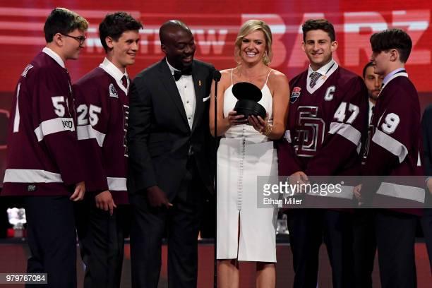 Network sportscasters Anson Carter and Kathryn Tappen present an award with Marjory Stoneman Douglas High School hockey team members Adam Hauptman...