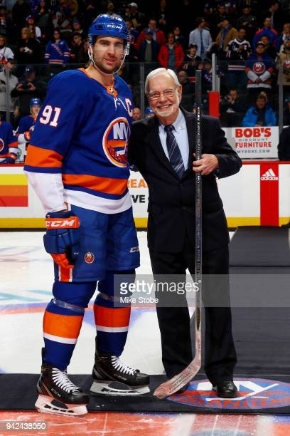 Networks hockey broadcaster Stan Fischler poses with John Tavares of the New York Islanders after receiving a commemorative silver stick during his...