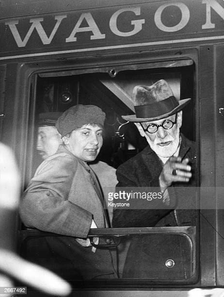Neurologist and a founder of psychoanalysis, Sigmund Freud at the window of a wagon-lit on arrival at the Gare de l'Est, Paris. He is accompanied by...
