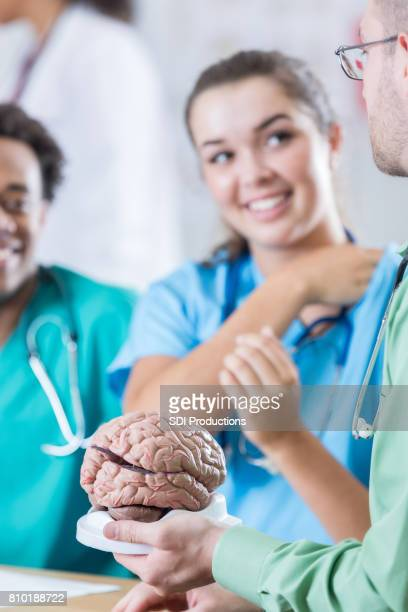 Neurologist talks with medical interns about human brain