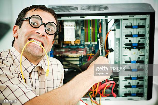 Neurotic male geek fixing his computer.