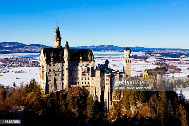 Schloss Neuschwanstein pronounced English New Swanstone Castle is a nineteenthcentury Romanesque Revival palace on a rugged hill above the village of...