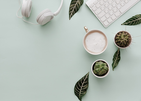 Neutral Minimalist Flat Lay Scene With coffee, keyboard, headphones and cactus 921591610