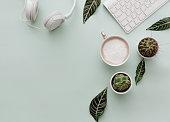 Neutral Minimalist Flat Lay Scene With coffee, keyboard, headphones and cactus