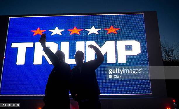Nevada caucus voters and Donald Trump supporters take a selfie in front of an electronic billboard truck parked in front of the Palo Verde High...