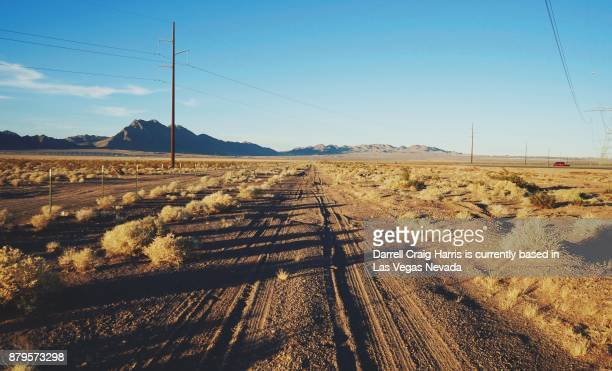 nevada desert road with power lines and poles in the background late afternoon - nevada photos et images de collection