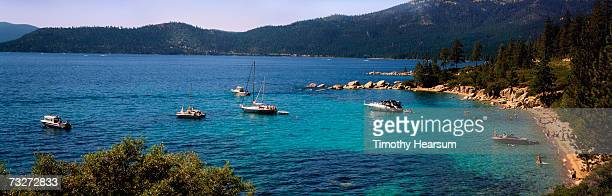 'USA, Nevada, Lake Tahoe, Sand Harbor, boats moored in lake off crowded beach'