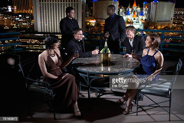 USA, Nevada, Las Vegas, Group of people sitting at round table on terrace, smiling, champagne bottle on table