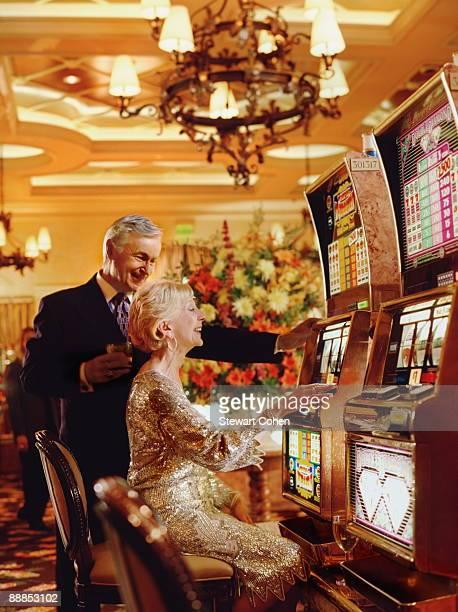 USA, Nevada, Las Vegas, Senior couple in casino playing on slot machines