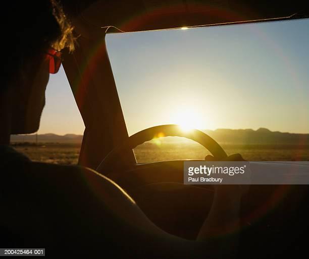 USA, Nevada, man driving in desert landscape, close-up, sunset