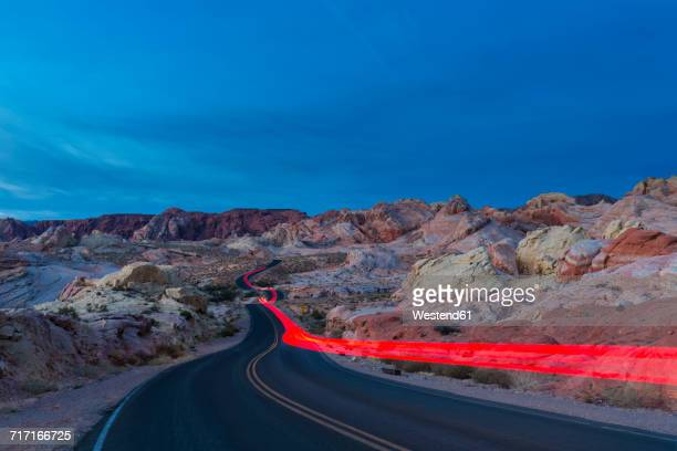 USA, Nevada, Valley of Fire State Park, sandstone and limestone rocks, light trails of a car on scenic road at twilight