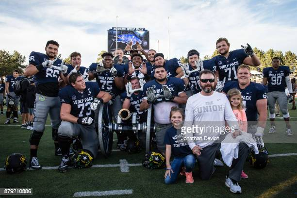 Nevada Wolf Pack offensive line coach Mason Miller poses with players and the Fremont cannon after the win over the UNLV Rebels at Mackay Stadium on...