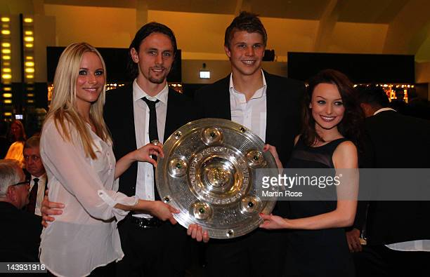 Neven Subotic and his girlfriend Teresa and Mitch Langerak pose with the trophy at View restaurant on May 5 2012 in Dortmund Germany