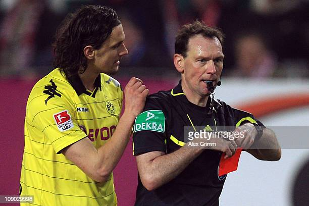 Neven Subotic of Dortmund discusses with referee Florian Meyer after being sent off during the Bundesliga match between 1. FC Kaiserslautern and...