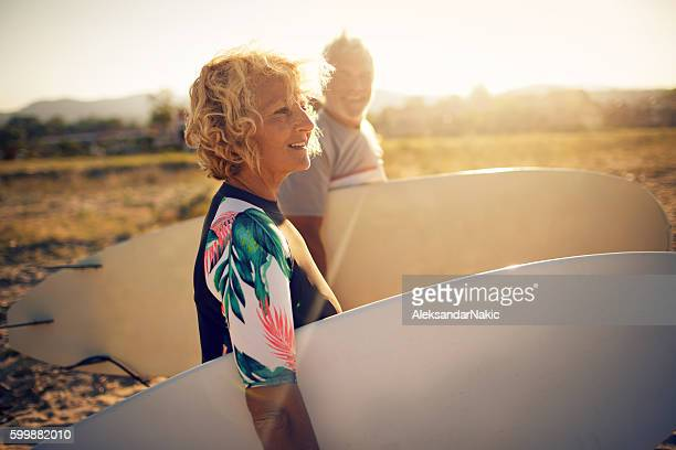 never too old for surfing - active senior woman stock photos and pictures